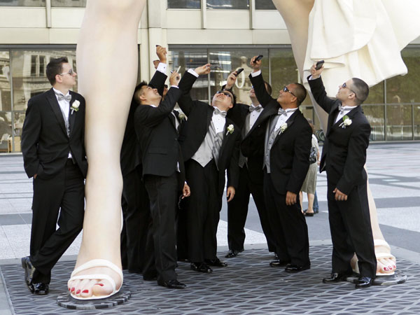 Male members of the Hugh and Anya Nguyen wedding party pose under Seward Johnson&#39;s 26-foot-tall sculpture of Marilyn Monroe, in her most famous wind-blown pose, on Michigan Ave. Friday, July 15, 2011 in Chicago.   <span class=meta>( AP Photo&#47;Charles Rex Arbogast)</span>